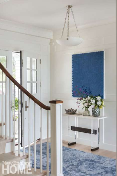 White entryway with blue painting Shingle-style home