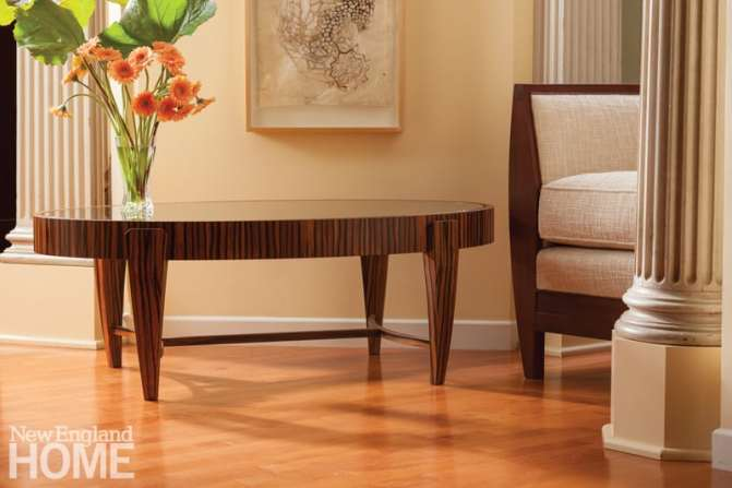 Tusk oval coffee table in Macassar ebony with a tempered-glass top.
