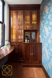 Big moments can be created in small spaces with the carefully planned design. Bold wallpaper in an unexpected bright blue hue adds oomph to traditional cabinetry.