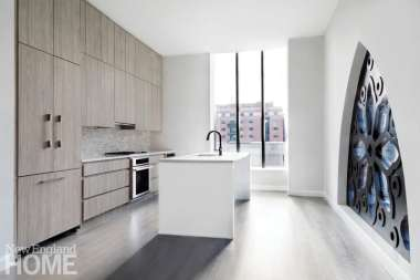 Kitchens at the Lucas boast gray wood-veneer cabinets, glass mosaic tile backsplashes, and glossy white islands.