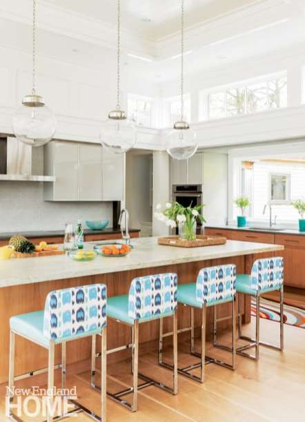A trio of Arteriors Reeves pendants dangles above the quartzite-topped kitchen island.