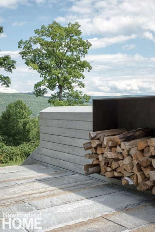 Wood for the upper terrace's elevated fire pit is stored in a steel crib.
