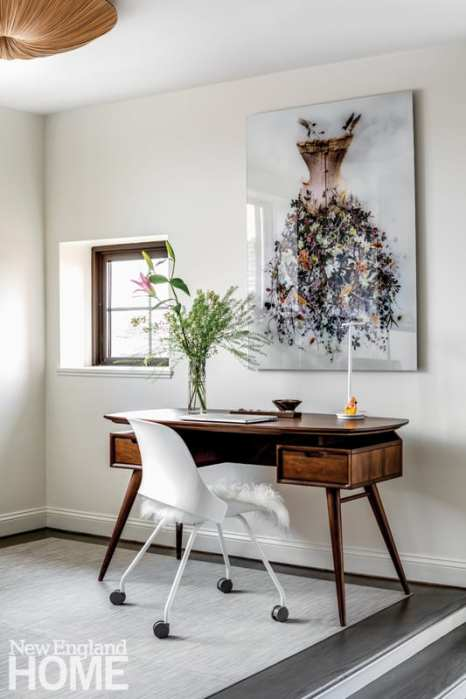 Office featuring painting of a dress above a dark wood midcentury desk and a white office chair with a furry seat