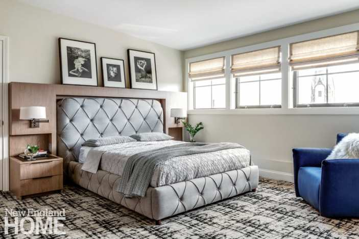 Master bedroom featuring gray bed, graphic black and white rug, and black and white photos above bed