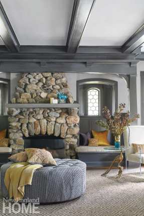 An oversized round ottoman in front of a stone fireplace and a nook with orange and purple pillows. There's also a glass and bronze accent table featuring a peacock base.