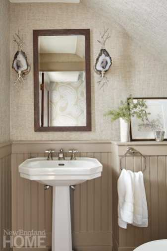 Power room featuring white pedestal sink, taupe wainscotting, white towel and agate sconces