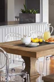 Wood tables topped with lemons, a pitcher of lemonade, white dishes and pastries
