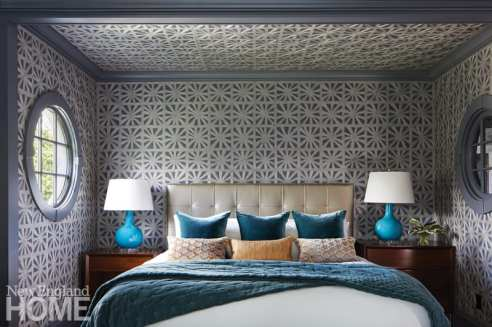 Bed in master bedroom with a portal window and wallpaper on the walls and ceiling. Blue lamps on the side tables.
