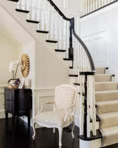 Stairway in the entry with a chair at the bast and a wood chest