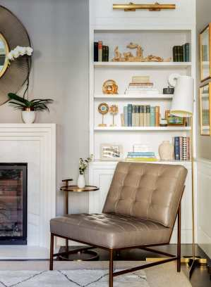 Detail of a leather chair next to a fireplace. Behind the chair is built in bookshelves displaying colorful books and art objects