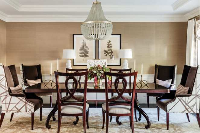 Traditional dining room table in dark wood with a chandelier hanging above and taper candles on top