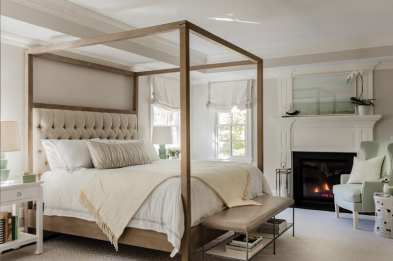 Bed in master bedroom with wood frame and canopy, pale green table lamps, bench at the end of the bed