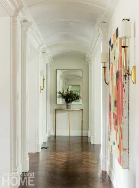 Hallway with sconces and are collection on the walls