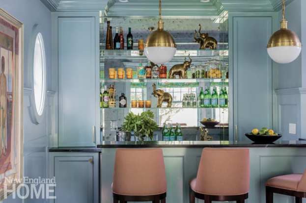 Mirrored bar with glass shelves for liquor. There's a bowl of lemons and limes on the counter and brass elephants on the bar back.