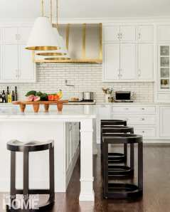 Kitchen with a white island and dark wood, backless bar stools. There's a tray on the counter stacked with red bell peppers, bananas, kale and turnips