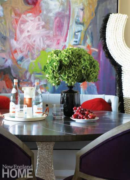 Dining table with zinc top and bold painting in the background