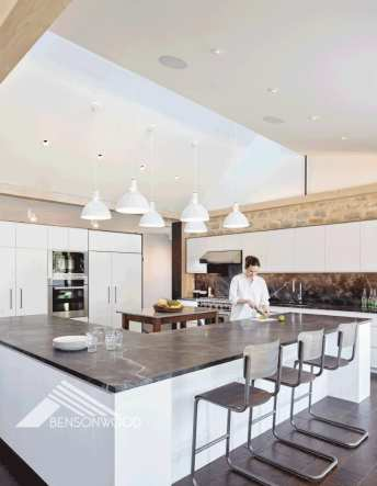 An open kitchen with a cook standing at the counter. The cabinets are white and the countertop is gray. There are three gray barstools at the counter and seven white pendant lights hanging from the ceiling.