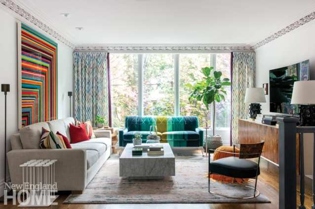 The living area featuring a couch upholstered in wide green and green-blue stripes, floor-to-ceiling windows that look out over trees, a pale taupe couch, a wood credenza and a large piece of art featuring rainbow-colored stripes
