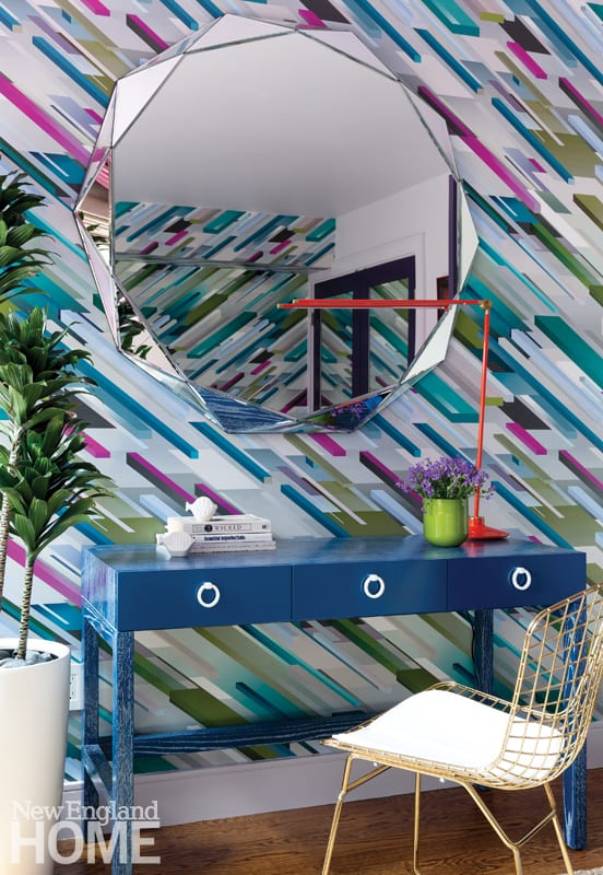 A large mirror hangs above a blue desk. There's a green vase of flowers on the desk and an orange lamp. The same geometric blue, purple, green and gray wallpaper is on the wall behind the desk.