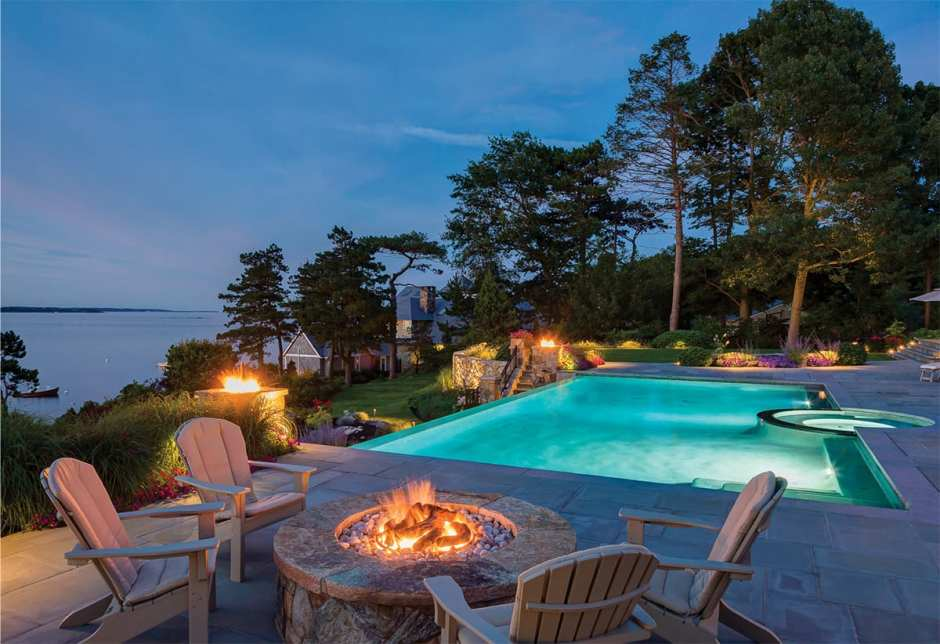 Picture of a pool and hot tub in the evening surrounded by fire pits and with a view of the ocean.