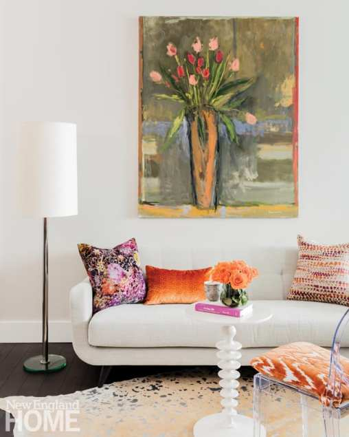 A white couch with throw pillows in oranges and purples. There is a large painting of tulips in a vase above the couch. The tulips are pink and red. There's also a cocktail table with a vase of orange flowers.