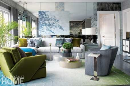 The condo's living room with a gray couch featuring throw pillows in shades of green, blue and gray. There's a green armchair and the walls behind the couch are mirrored.
