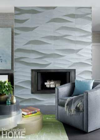 A gray fireplace with a wave pattern design. There's a dark gray armchair with a blue accent pillow.
