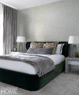 Guest bedroom bed in dark green. The bed covers are white and gray. There's gray carpeting on the floor. Nothing hangs above the bed.