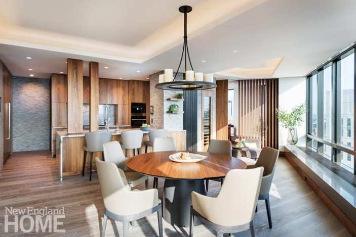 Round, walnut dining table surrounded by taupe colored chairs with a view into the walnut kitchen