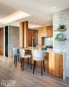 Kitchen with walnut cabinets and three taupe barstools. There are green plants on the walnut shelves hanging from the gray tiled walls.