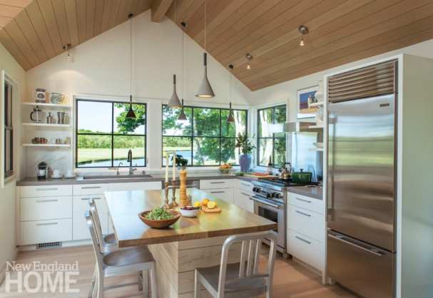 Kitchen with white cabinets and stainless-steel appliances. Pendant lamps hang from the pitched ceiling above a dining room table. Three windows look out onto the yard.