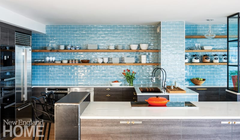 Large open kitchen with blue subway tile backsplash from the countertop to the ceiling. Open shelving featuring dishes. Stainless steel appliances.
