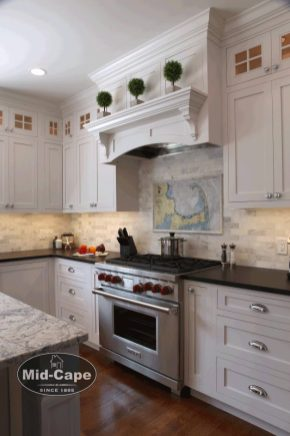 Mid-Cape Home Centers Kitchen with white cabinets, marble counters and a stainless steel oven with red knobs