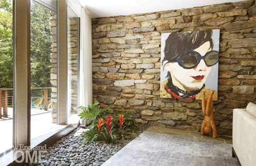 Living room with an in-ground planter featuring tropical plants. Behind the planter is a stone wall with a large painting of a woman in sunglasses.