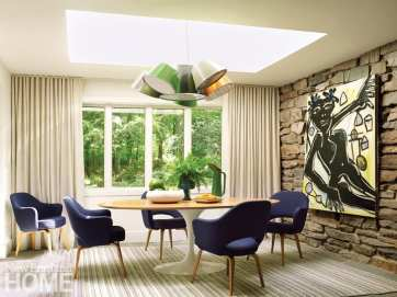 Dining room with a round would table and midcentury chairs covered in navy blue. There's a stone wall with a painting of a woman on the wall.