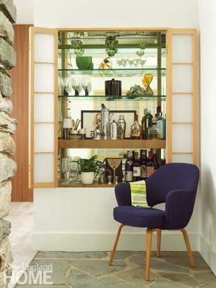 Built-in shelves stocked with barware and liquor. There's a midcentury chair covered in navy blue in front of the cabinet.