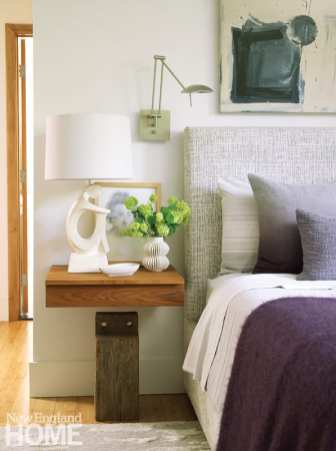 Close up shot of the side of a bed with a gray headboard and white and eggplant bedding. There's a floating nighstand with a lamp and a vase of hydrangeas.