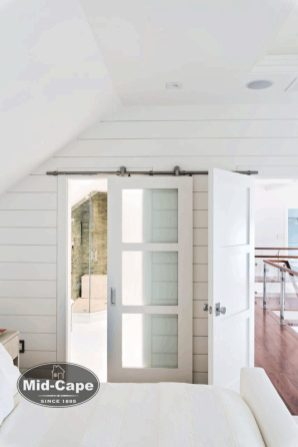 Room with white shiplap walls and a glass barn door