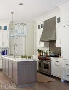 Kitchen with gray cabinets and stainless appliances. There are artichokes on the marble countertops.