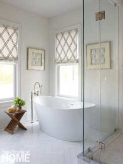 Bathroom with freestanding white tub, white herringbone tile floor and glass shower