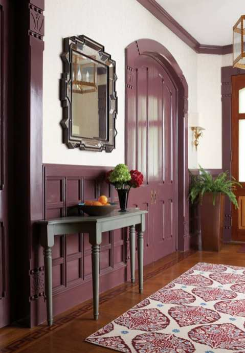 Entryway with purple doors, wainscotting and trim. There's a wood floor with a patterned rug and an accent table in dark gray.