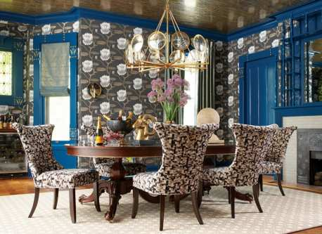 Dining room with blue trim and doors, and lotus-patterned wallpaper. There's a six-person wood dining table with chairs upholstered in a black, brown and white geometric pattern.