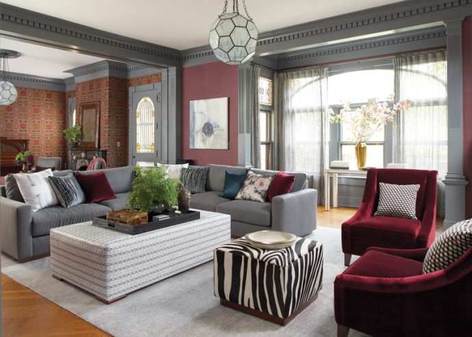 Conversation area in the living room featuring a gray couch and deep red velvet side chairs and a zebra-print ottoman