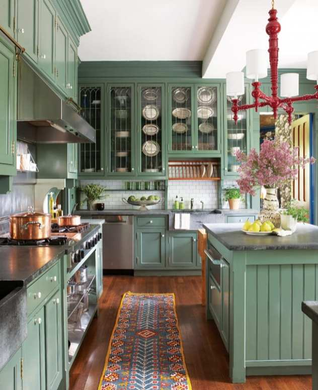 Kitchen with green cabinets and a red light hanging over the island
