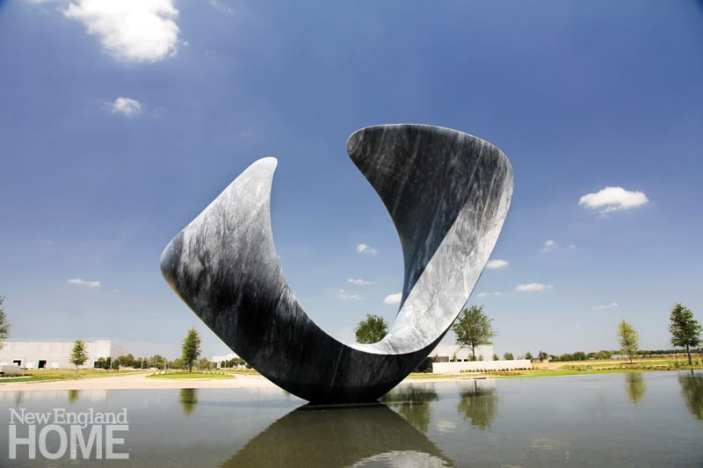 Monumental gray marble sculpture in a shallow pool of water