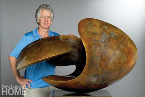 The artist wearing a blue polo shirt and khaki bottoms. He's standing behind an abstract marble sculpture.