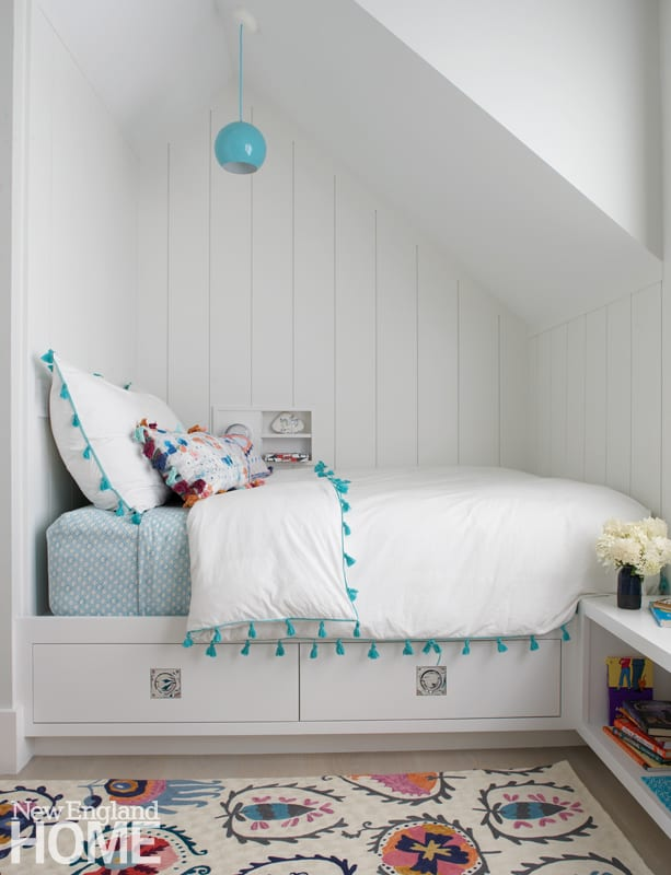 Two more girls cozy up in a room with built-in beds that incorporate helpful storage.