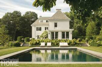 The back of a white house with a swimming pool in front of the house. There are white hydrangeas behind the pool.