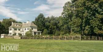 an expansive green lawn with a cedar fence and a white home beyond the fence