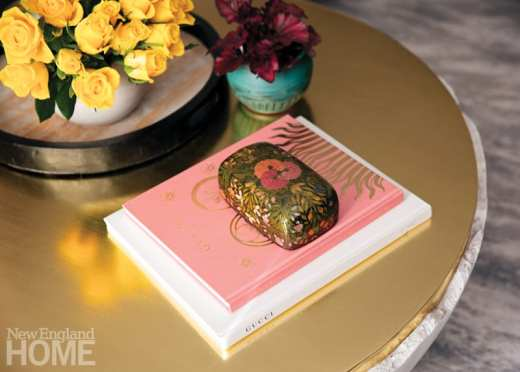 Top of a coffee table with a vase of yellow flowers and two books